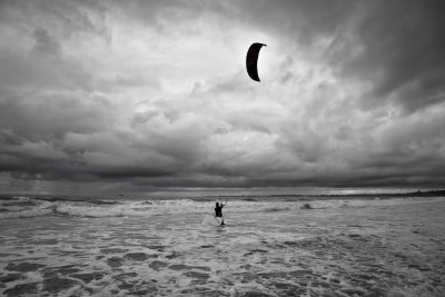 Kitesurfer gets in the water during a storm.